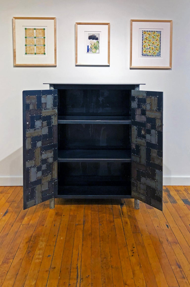 This is a totally functional two-door cupboard. It is created from hot rolled steel and found steel. The legs are made from salvaged pipe. The panels on the door fronts and sides are made from salvaged pieces of steel with the original paint and