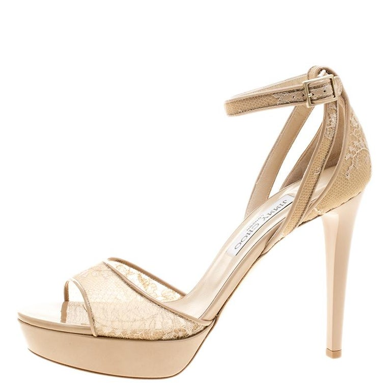 Coming from the house of Jimmy Choo, these nude Kayden sandals are set on a platform sole and slender heels. It comes with a delicate beige lace body and detailed with patent leather. Secured with an ankle strap closure, this pair can effortlessly