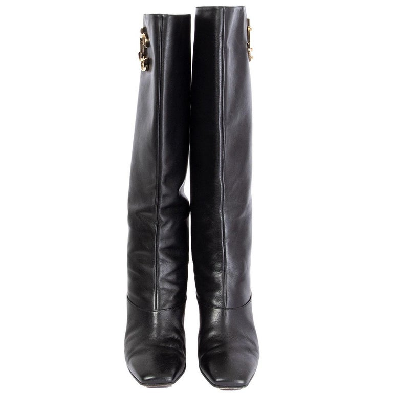 100% authentic Jimmy Choo 'Mahesa' boots in black leather embossed with light gold-tone JC logo on the shaft. Have been worn with some soft patina allover and a small dent on the inside of the left heel. Overall in very good condition.