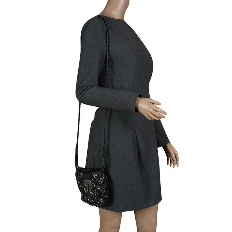 This suede-lined Jimmy Choo bag is the perfect accessory to go with your outfit for any event. Made in black leather, it is incredibly sleek and goes well with any kind of getup. Combine class and splendor, complement your evening ensemble with this