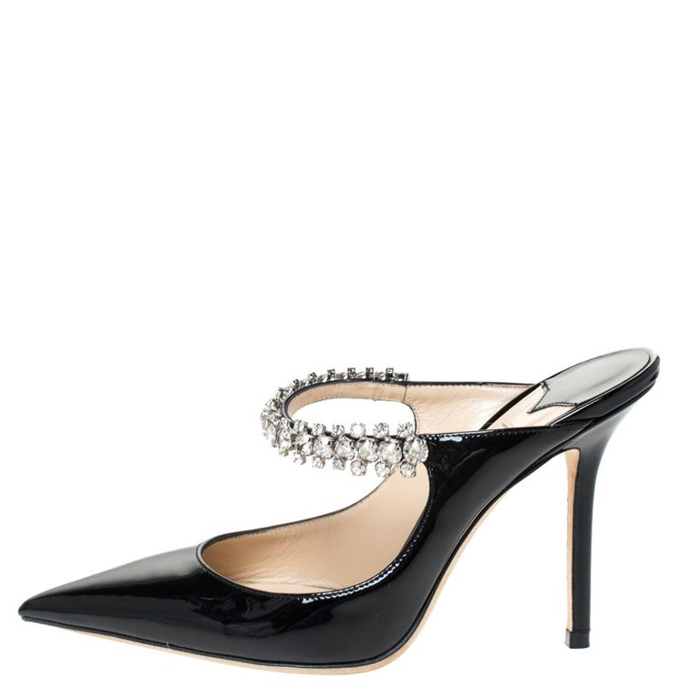 Designed to impart a resolutely feminine appeal, Jimmy Choo's Bing shoe is for fashionable expeditions. The mule features a patent leather pointed toe and a single strap adorned with crystals. The delicate shoe is elevated by a slim heel.