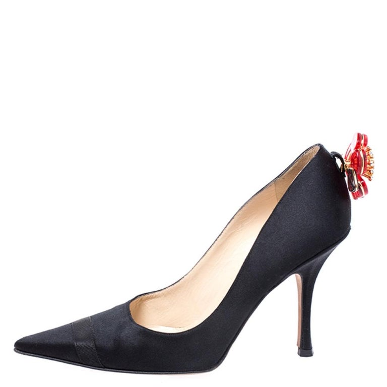 This pair of Jimmy Choo pumps is a style statement and a timeless piece. Sporting a fine satin exterior, these pumps are designed with pointed toes, high heels and flower applique on the counters. Subtle and stylish, this pair of black pumps win you