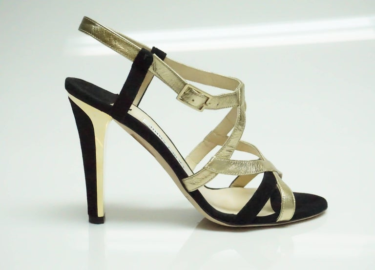 Jimmy Choo Black Suede and Gold Metallic Leather Strappy Heel - 39  These modern heels are in excellent condition and have a very sharp look to them. The Heel has a gold metal accent around the black suede. They have little to no wear on the inside