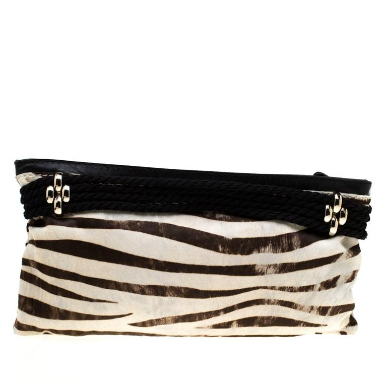 Chic and very stylish, this clutch from Jimmy Choo deserves all your attention! The black and white clutch is crafted from calfhair and features a zebra print. It has been styled with a gold-tone buckle strap on the front and opens to an Alcantara