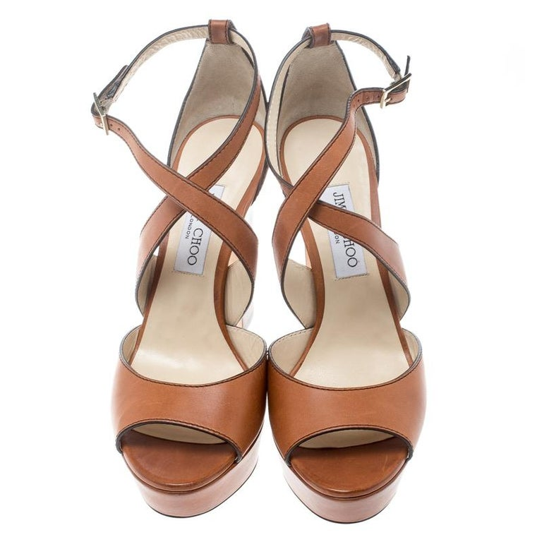 These sandals from Jimmy Choo are utterly gorgeous! The sandals are crafted from leather and designed with cross straps ending as wraps around the ankles. Balanced on block heels and platforms, this lovely pair will have everyone in