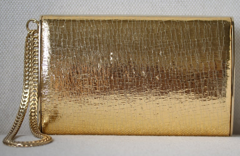 Jimmy Choo gold leather and metal clutch with wristlet chain. Satin-lined interior. Made in Italy.  Dimensions: Approx. D 4 cm  x H 10 cm  x W 15 cm   Condition: Excellent pre-owned condition, no sign of wear except superficial scratching to