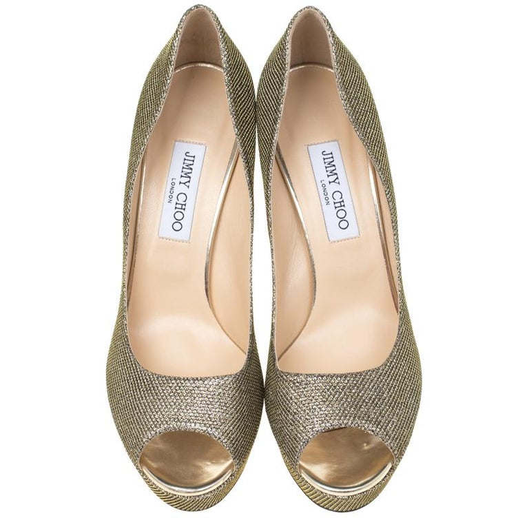 Flaunt an elegant look in this pair of Dahlia pumps from Jimmy Choo. Ideal for glitzy events, they are crafted from metallic light bronze, lamè glitter fabric and come with peep toes, platforms, and 12.5 cm gold-tone stiletto heels. Exquisitely