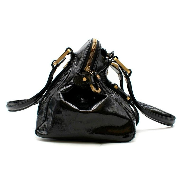 Jimmy Choo Malena Black Patent Leather Handbag    - Black patent leather handbag  - Suede contrast panel  - Top handles  - Front and back strap detailing  - Front metal hardware with logo engraved  - Front zipped pocket  - Zip fastening  - Internal