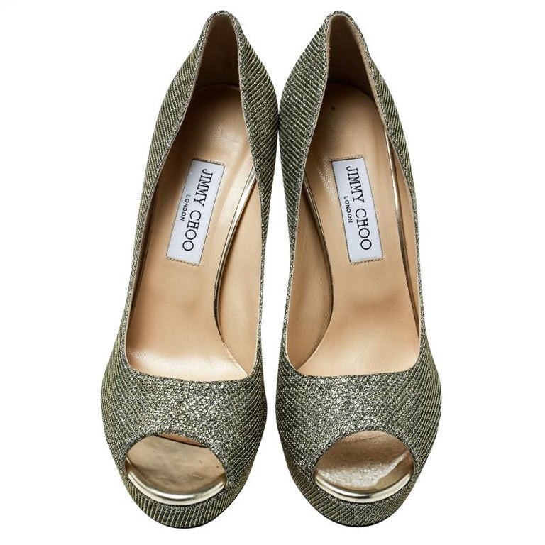 Look no less than a diva in these Dahilia pumps from Jimmy Choo. Crafted from metallic champagne lamè fabric, they are lined with leather on the inside. This pair carries 12.5 cm high heels with supporting platforms. Complete with peep toes, you can