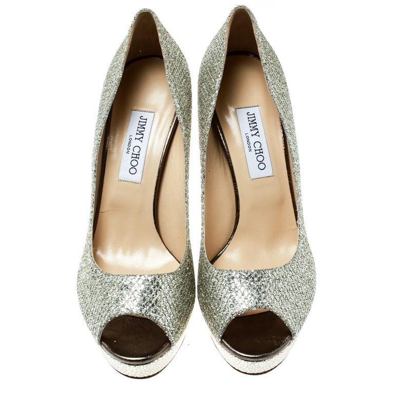 Look no less than a diva in these Dahilia pumps from Jimmy Choo. Crafted from metallic gold lamè fabric, they are lined with leather on the inside. This pair carries 12 cm high heels with supporting platforms. Complete with peep toes, you can