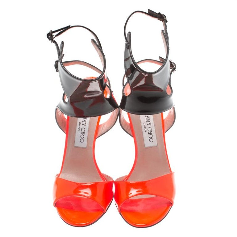 These sandals from the house of Jimmy Choo are a fine blend of comfort and edge. Crafted from patent leather, these come in black and orange with looped ankle cuffs and 11.5 cm heels. Glam up your outfit with these open-toe sandals.  Includes: The