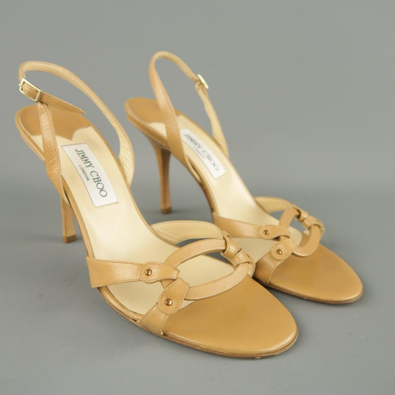 JIMMY CHOO sandals come in tan leather with a sling back, covered stiletto heel, and loop detailed toe straps. Wear on heel. As-is. Made in Italy.   Good Pre-Owned Condition. Marked: IT 42   Measurements:   Heel: 4.5 in.