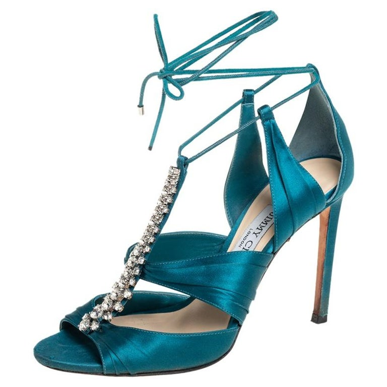 Never go out of style with this classy pair of sandals from the house of Jimmy Choo. Have everyone look at you in admiration with these teal blue satin sandals that are styled with open toes, crystal embellishments on the vamps, and self-tie ankle