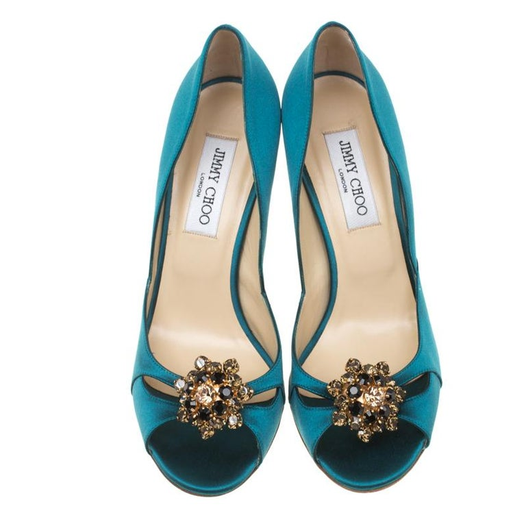 How gorgeous are these turquoise blue sandals from Jimmy Choo! They have been crafted from satin and styled with peep-toes. They flaunt a cut-out design on the vamps and an exquisite crystal embellishment detailing. They come equipped with