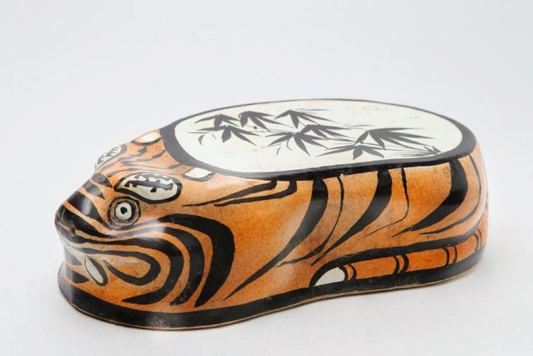 TIGER PILLOW , JIN DYNASTY, 12TH CENTURY (c. 1150)  The pillow is assembled with a hollow construction, its molded form covered with a white slip. An orange brown slip is applied to the body, excluding the back, ears and eyes which remain white;