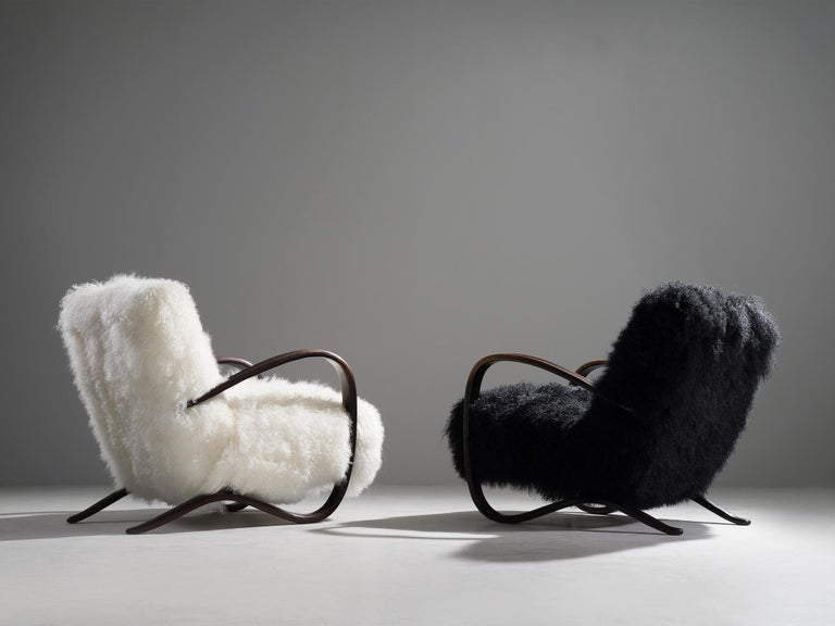 Jindřich Halabala, customizable lounge chairs, beech, Tibetan wool, Czech Republic, 1930s  Extraordinary black and white easy chairs with Tibetan lamb's wool upholstery. These chairs have a very dynamic and abundant appearance and the fuzzy