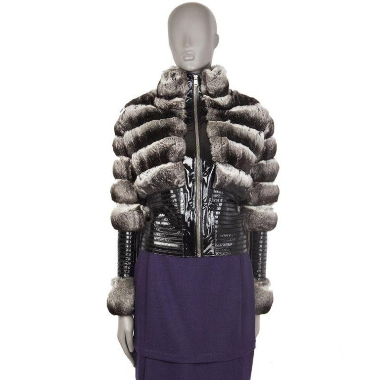 Jitrois high-nech fur jacket in black,, grey, and off-white chinchilla and black patent leather.  With patent strips panelled on black silk (60%), nylon (30%), and lycra (10%). Features zipper closures on the sleeves and on the front. Has been worn