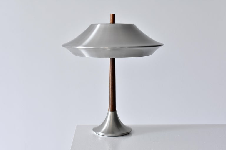 A table lamp designed by Jo Hammerborg. Produced by Fog & Mørup in the 1960's. Executed in Aluminium and Rosewood.   Jo Hammerborg, trained at the Royal Danish Academy of Fine Arts, served as design head at Fog & Mørup. Prior, Hammerborg worked as