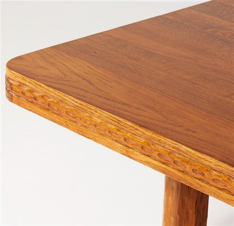 Early Scandinavian Modern library table by Swedish architect and designer Joel Norborg. Executed in oak, pine and iron rivets. Hand carved & sculpted relief details to the slab and legs. The table was manufactured, circa 1910. Norborg (1880-1971)