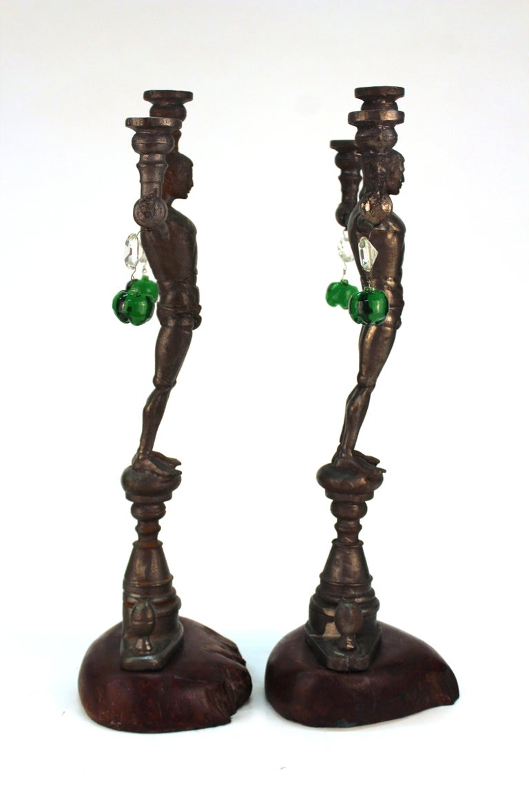 A pair of cast iron candelabras in the shape of G.I. Joe action figures in the nude with stretched out arms, created by California artist Joel Otterson (b. 1959) in circa 1992. The pair has hanging lead crystal elements and is affixed to wood bases.