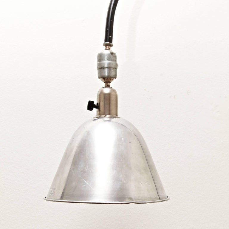 Wall lamp designed by Johan Petter Johansson. Manufactured by Triplex (Sweden), circa 1930. Aluminium and steel.  In good original condition with minor wear consistent with age and use, preserving a beautiful patina.