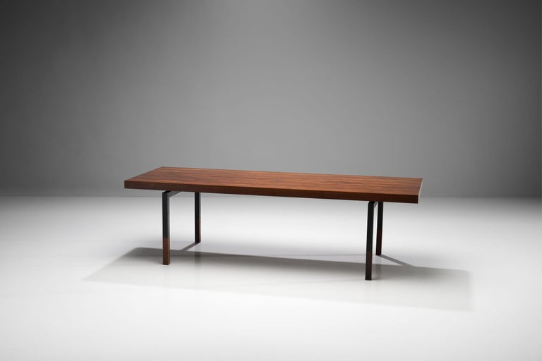 This table is a modern Danish rectangular wooden coffee table, with a black lacquered metal frame designed by Johannes Aasbjerg Andersen. The table was manufactured by the historical manufacturer, Illums Bolighus. The tabletop and bottom of the legs