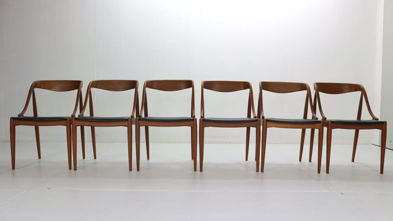 Beautiful set of six dinning room chairs designed by Johannes Andersen for Uldum Møbelfabrik, 1960s Denmark.  The chairs are made of solid teak wood frame. Organic form frame provides not only elegant Danish design but comfortable seating.  Black
