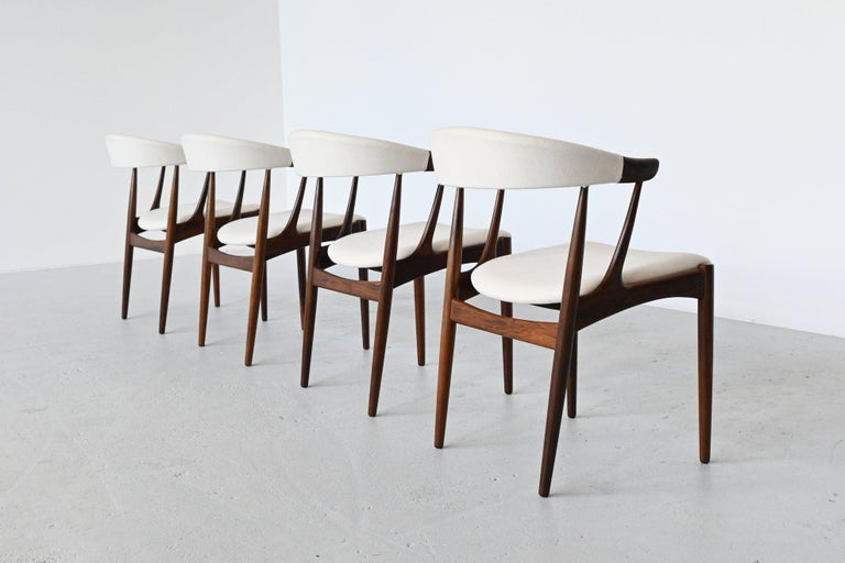 Stunning set of dining chairs model BA113 designed by Johannes Andersen and manufactured by Brdr. Andersens Møbelfabrik A/S, Denmark 1969. The chairs features a solid rosewood frame and they are newly upholstered with white Divina upholstery from