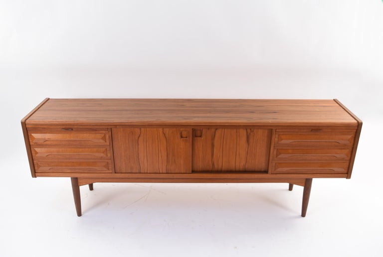 This interesting Danish midcentury teak sideboard was designed by Johannes Andersen in the 1960s and is attributed to Kofod-Larsen as the maker. This piece features the quintessential recessed square cabinet door handles of Andersen's design. The