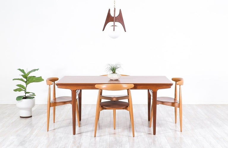 Stylish Danish modern draw-leaf dining table by Danish furniture designer Johannes Andersen and manufactured by Uldum Møbelfabrik, circa 1960s. This versatile table design features a solid teak wood body with a rectangular top and angled tapered