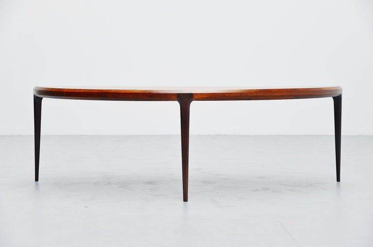 Nice moon shaped rosewood coffee table designed by Johannes Andersen and manufactured by CFC Silkeborg, Denmark 1960. This very nicely finished coffee table with very nice and deep rosewood grain to the wood can finish your interior into perfection.
