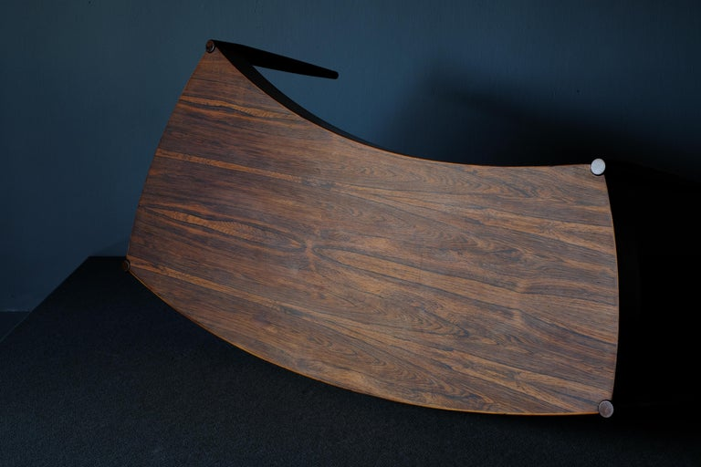 Really unique curved coffee table. It has sculptural lines and elegant tapering legs. It was designed in the 1960s by Johannes Anderson and produced by Trensum. The wood has a lovely grain and it's patina has been allowed to develop. Quite the