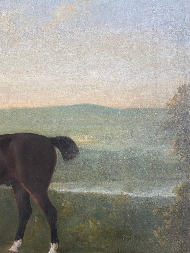 A large 18th-century painting chestnut Horse and a young bay stallion with two accompanying dogs in an extensive English landscape. Oil on canvas in a period giltwood frame.   Dimensions: 117 x 142cm (46 x 56in.)  Provenance:   Canterbury Auction