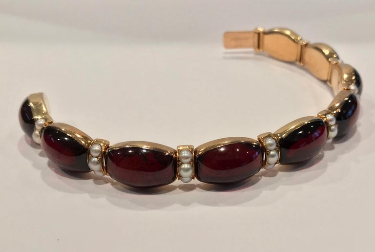 John Brogden Signed Gold Carbuncle and Pearl Bracelet, C.1855. The bracelet is formed of nine bezel set oval shaped cabochon garnets each interspaced with articulated sections of pearls, three in each, total of twenty seven.  terminating with