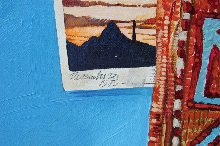 The painting depicts an orange/red toned rug centered on a bright blue background with a small image peaking out from underneath the rug. The small photograph has a gold ring set on top of it and includes a date written on the bottom (December 20th,