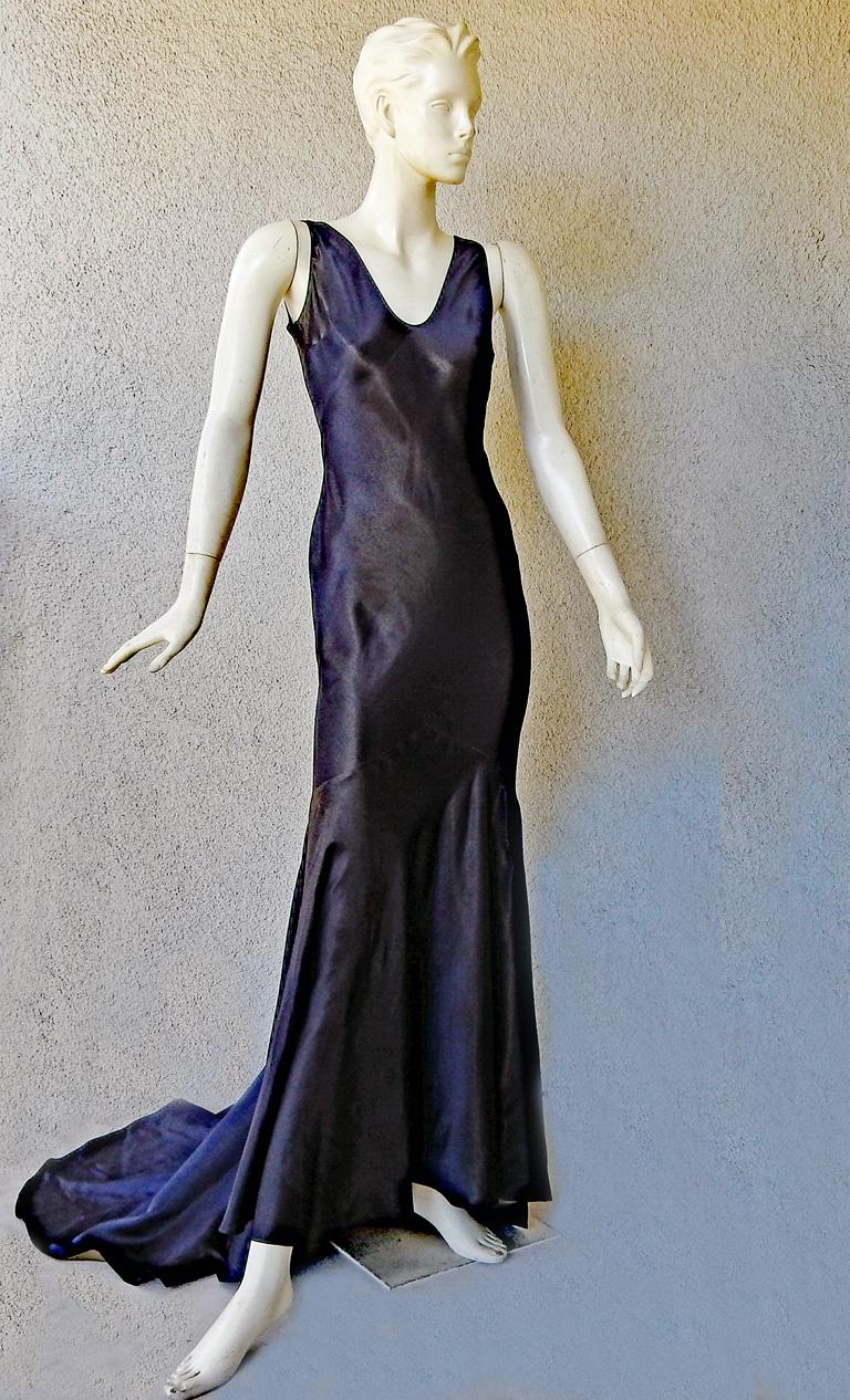 Lovely Harlowesque 1930's style bias cut gown by John Galliano.   Fashioned of navy silk backed in antique gold silk interior.  V neckline and deep drape open back.  Excellent tailoring boasts godet panel skirt.  Overhead entry.  Designed at a time
