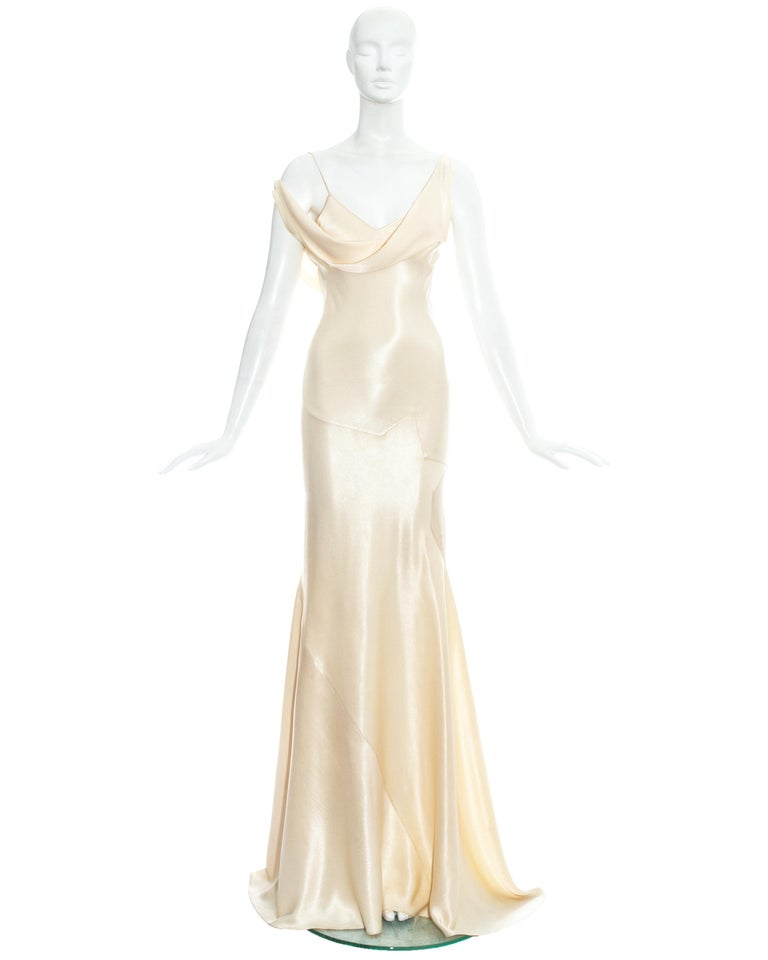 John Galliano; champagne rayon bias cut wedding dress.     - Spaghetti straps   - Draped cleavage with one strap designed shorter to be worn off the shoulder   - Signature Galliano half-star shaped panels around hips   - Bias cut panels cut to