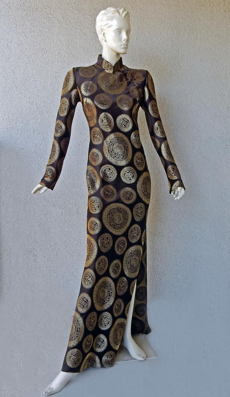 An original John Galliano coveted cheongsam vintage gown.    Fashioned in rich silk chocolate brown with Chinese gold medallion print.   Features a seductive high side slit. The combination of fabric and lighting offers a rich distinctive presence