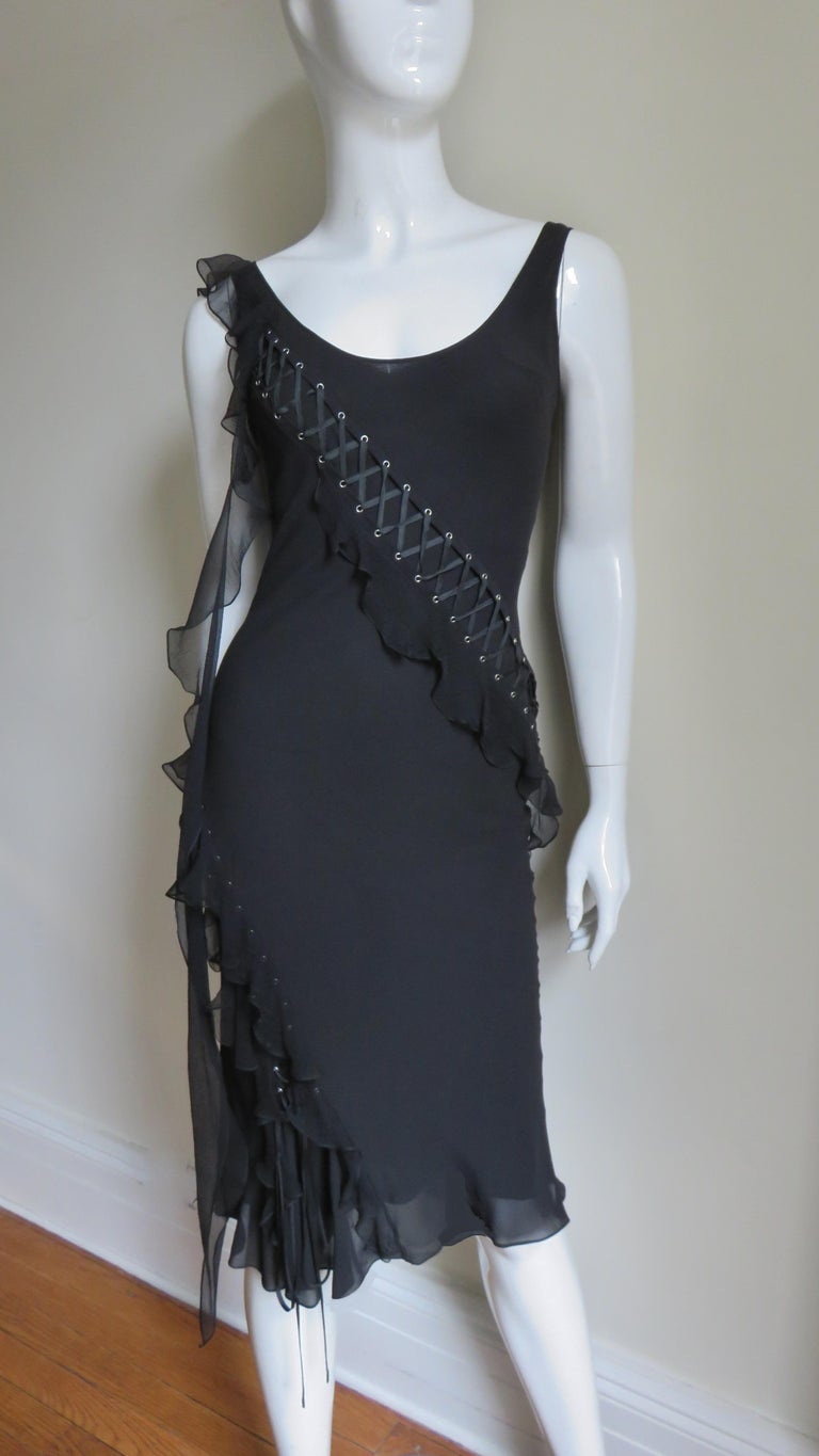 A fabulous black silk dress from Christian Dior.  It has a scoop neck front and back with intricate lacing starting at each shoulder across the front/back around the hips to the hem.  Small silver grommets are laced with a fine silk ribbon which is