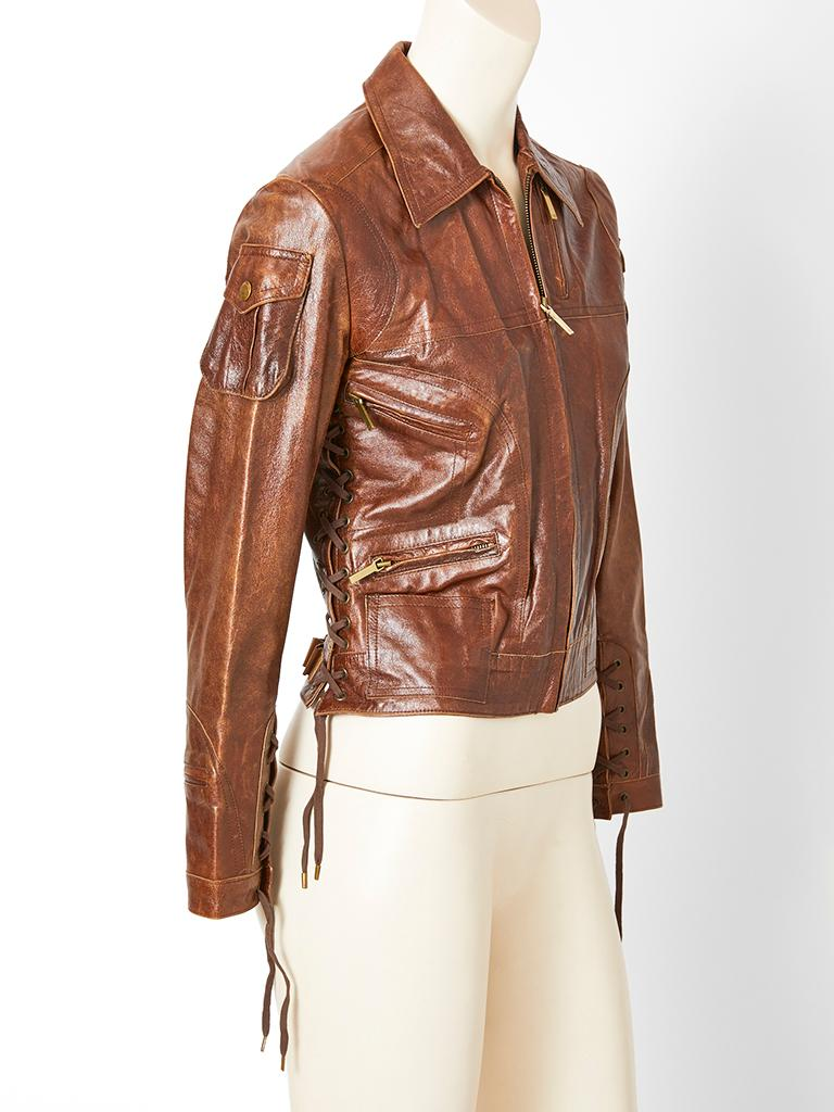 John Galliano for Christian Dior, brown, distressed  leather, fitted, cropped jacket, having small flap pockets at the shoulders, slanted zipper compartments at the bust, hip and cuffs and lacing detail at the sleeves and sides.