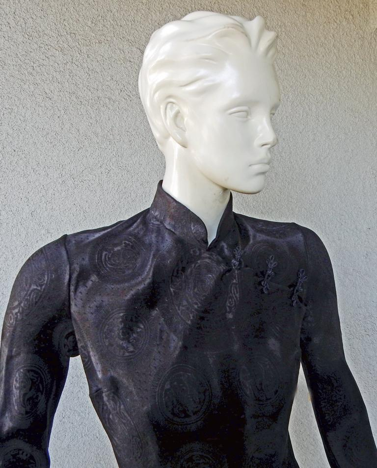John Galliano's signature cheongsam style dress offered in new condition.   Fashioned of medallion embossed black jacquard silk.  Wonderful drape to the body with high side slit and over head entry.  A rare perfect Galliano vintage cheongsam