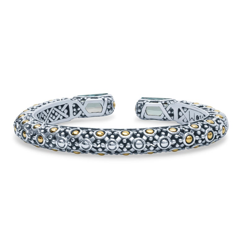 John Hardy 925 sterling silver cuff bracelet with two elongated radiant cut blue topaz with 18K yellow gold accents throughout the bracelet.  Matching ring sold separately.