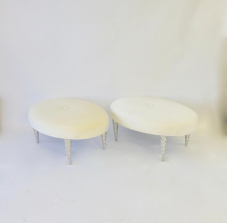Elegant and sensual oval ottomans designed by John Hutton. Brought in by Angelo Donghia Hutton was director of design 1978 - 1998. This pair covered in cream and white ultra suede are in excellent original condition.