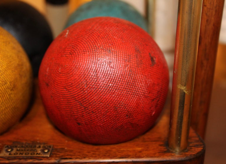 A large four player Croquet set on oak stand, complete with balls, hoops and post, bearing brass plaque inscribed John Jaques & Son, Makers London, early 20th century.