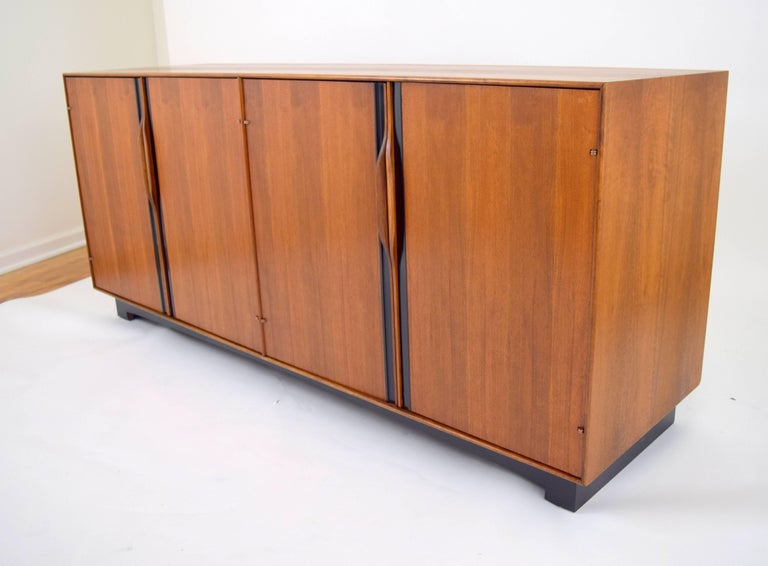 John Kapel for Glenn of California walnut credenza or sideboard with sculpted walnut handles and black plastic inlay. Four doors conceal one adjustable interior shelf on each side, and two shallow drawers on one side. Lovely oiled walnut case with