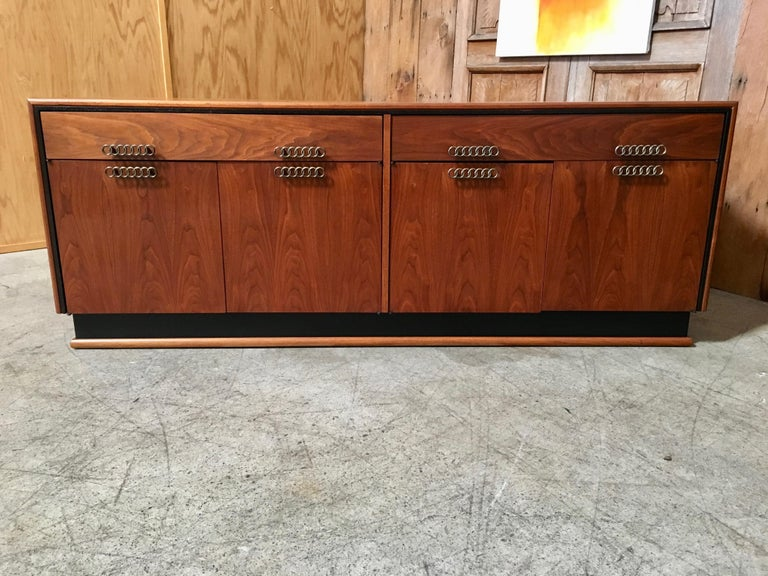 Stunning walnut with black accents two drawers over four doors with seven ring linked drawer pulls and adjustable shelves.