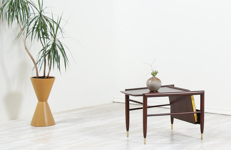 Stylish Mid-Century Modern side table designed by John Keal for Brown Saltman in the United States, circa 1960s. This modern side table is crafted in sturdy walnut-stained mahogany with brass sabots in all four legs. The top is complemented by a