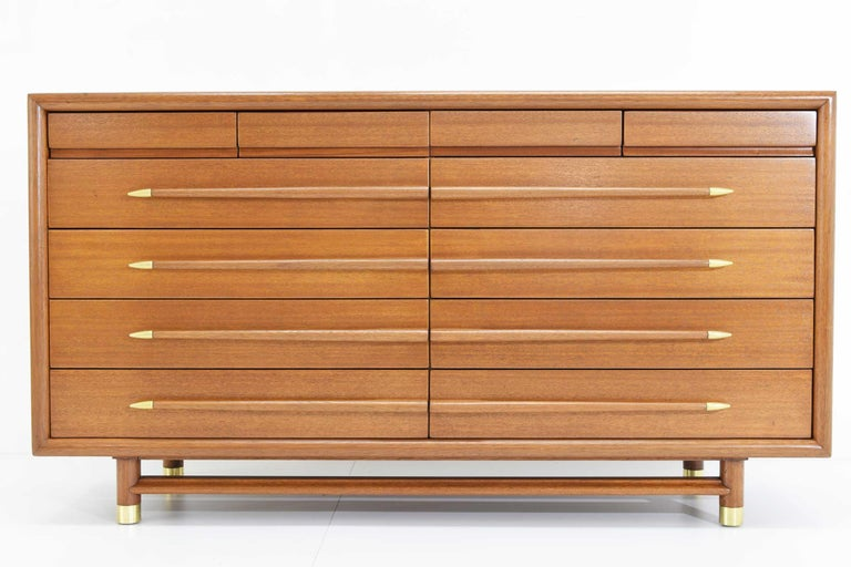 Beautifully restored chest of drawers by John Keal. Walnut 12-drawer dresser with sculptural pulls terminating in polished metal tips by John Keal for Brown-Saltman, 1950s. Back stamped with 9013 and Mr. & Mrs. A substantial piece with brass sabots