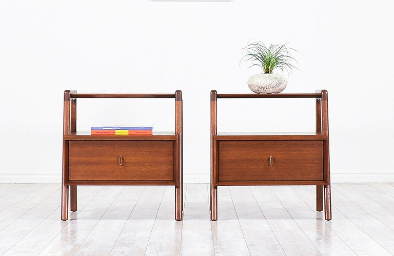 A pair of elegant modern nightstands designed by John Keal for Brown Saltman in the United States, circa 1960s. This fabulous pair of nightstands are built on solid walnut-stained mahogany wood featuring a single sculpted drawer to store bedside