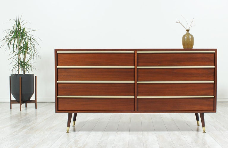 Spacious dresser designed by John Keal for Brown Saltman in the United States circa 1950s. This six-drawer dresser features a walnut wood case with long, brass pulls on each of the dovetail-constructed drawers. This exceptional dresser sits on four